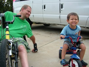 A father on a handcycle smiles as he watches his son riding his tricycle