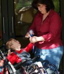 Young child with physical and development disabilities gets a toy from his mom