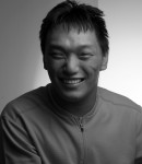 Young Asian man with developmental disabilities smiles for the camera (in black and white)