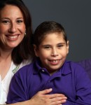 boy with a physical disability smiles with his mother