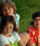 3 girls with developmental disabilities smile for the camera