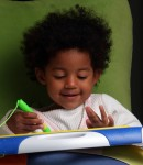 Young African American Girl playing with drawing toy
