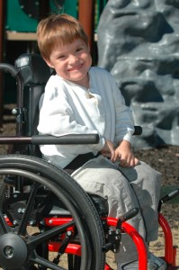 Young child similing from his wheelchair
