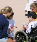 Little boy contemplates sharing his stuffed whale with a fellow Miracle League player