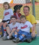 Group of young Miracle league baseball players sit and relax with their coach