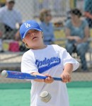 Boy with Downs hits the baseball with his bat