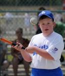 Young man with intellectual disabilities swings the bat at an incoming ball