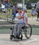 Man in a wheelchair swings the bat at a local baseball game