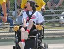 Young wman with intellectual and physical disabilities smiles as she's wheeled to home plate
