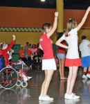 Inclusive shot of girl in a wheelchair cheerleading alongside two able-bodied girls