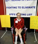 Teenage girl in wheelchair in front of sign which calls for the Elimination of the APD Waitlist in Florida