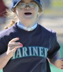 Young girl with Downs Syndrome runs towards the base in an inclusive game of baseball
