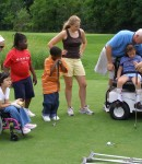 This is shot of inclusive golf featuring several people golfing with varying severity of disability
