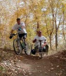 Image of two bikers on a nature trail, one handcycling and the other biking