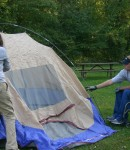 Image of two people working together to put up a tent