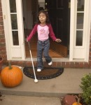 young girl with a visual impairment uses her cane to exit her home