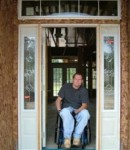 Man with a physical disability poses in his doorway