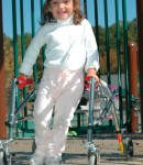 Girl with a walker plays on the accessible playground