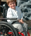 A young boy in a wheelchair gives a nice smile for the camera
