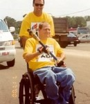 Man in a wheelchair holding the torch during an ADA marathon