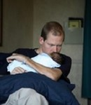 Father holds his newborn baby at the hospital
