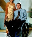 Husband and wife pose for a fomal photo while on a cruise (man uses a wheelchair)