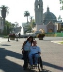Couple poses in front of a church while on vacation (man has a physical disability)
