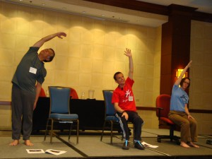 This image shows conference participants leading an adaptive yoga exercise