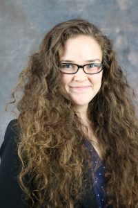 Picture of Meagan Sullivan, white female with brown curly hair and glasses