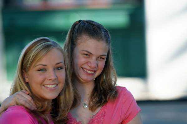 Teenage girl with developmental disabilities smiling with her big sister