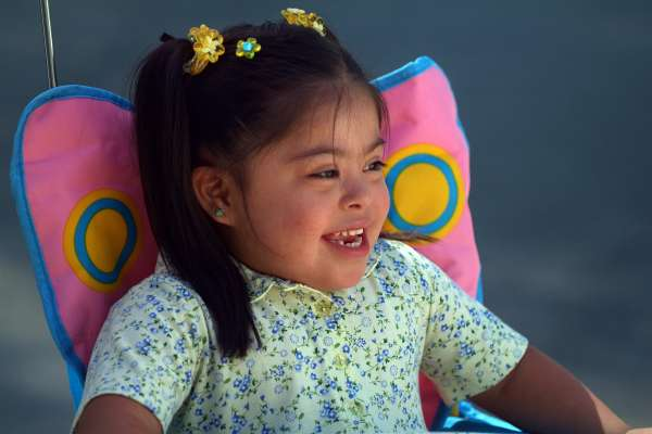 Young girl with Downs in pigtails sitting in a kids chair