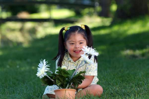 Young girl with Downs Syndrome smiles with a potted plant