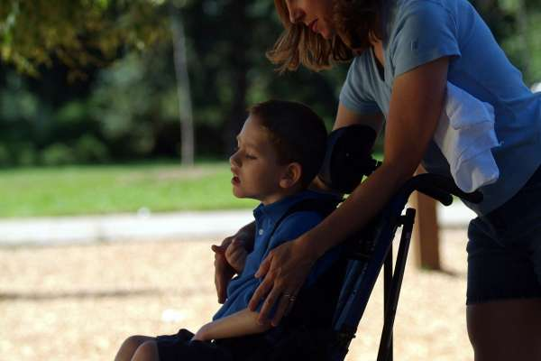 Side view of boy with physical and developmental disabilities and his mother