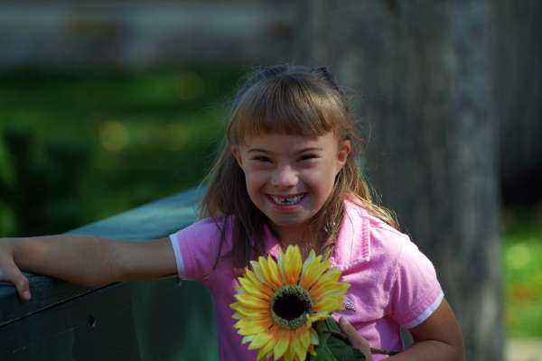 Young girl with Developmental Disabilities holds a sunflower