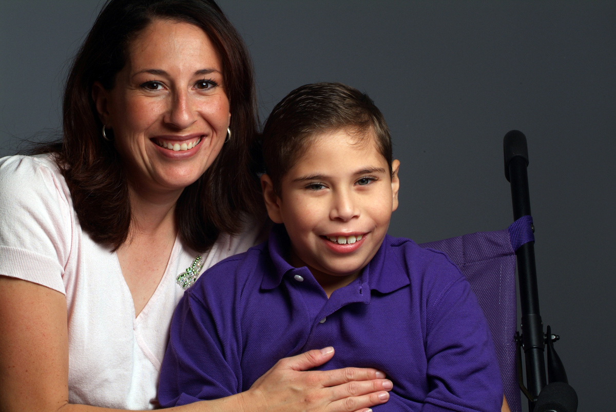 Proud mother and son using a wheelchair embrace and smile for the camera