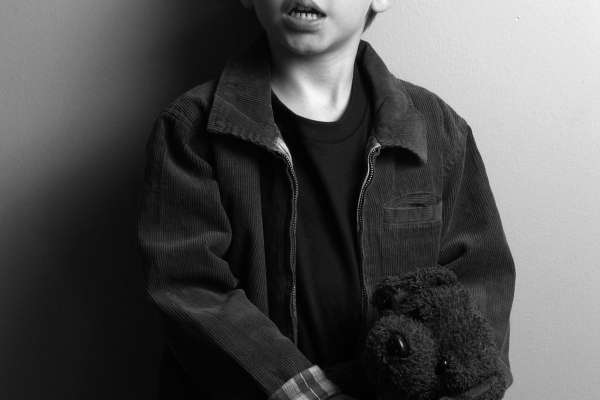 Full shot of young boy with vision impairment (in black and white)
