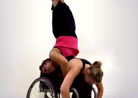 Two dancers balancing in an armstand pose (the dancer on the base is in a wheelchair)