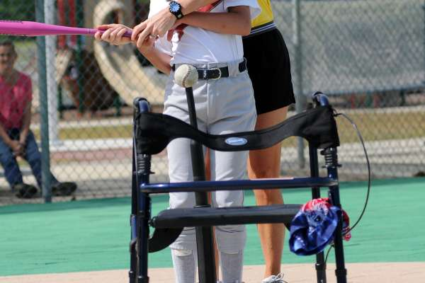 Miracle League player gets help hitting the tee ball from her baseball coach