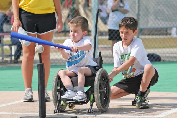 Young boy with a physical disability hits the teeball