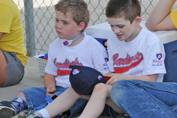 Two young Miracle League players take a break from the game