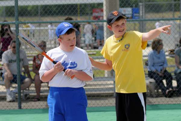 Teenage boy helps by coaching his player at local baseball game