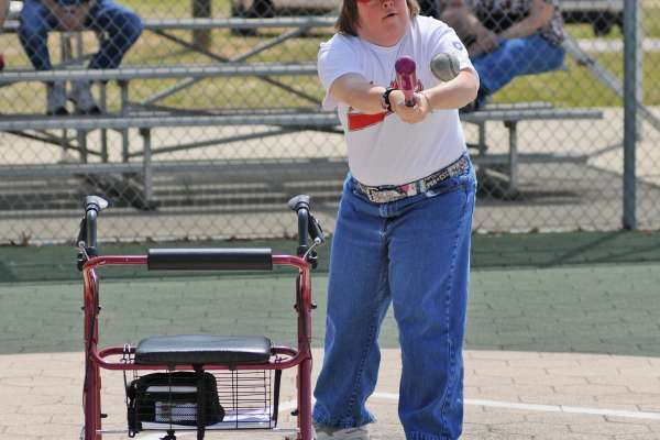 Woman sets aside her walker to swing the bat at a local baseball game