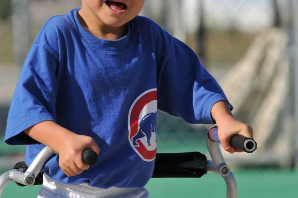 Young boy in baseball outfits runs the bases with his walker