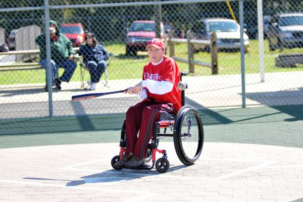 Young man swings the bat from his wheelchair