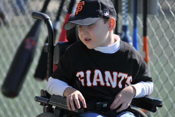 YOung boy in a Giants jersey and hat looks to his side from his wheelchair