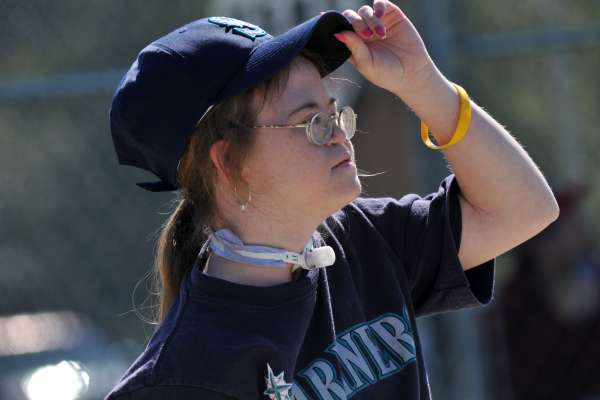 Young woman lifts her Mariners cap to see if the bases are loaded
