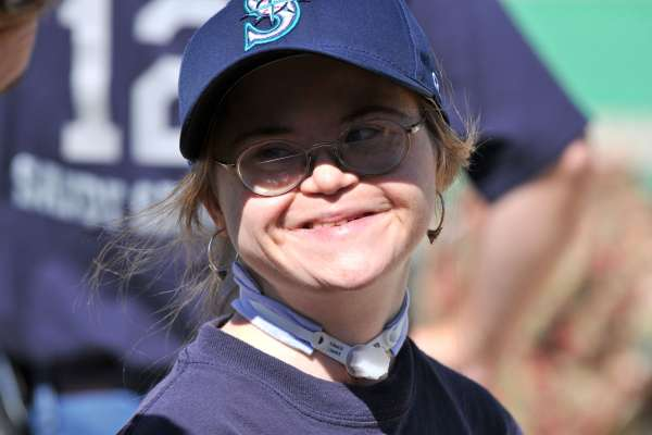 Young woman with intellectual disabilities and glasses smiles for the camera