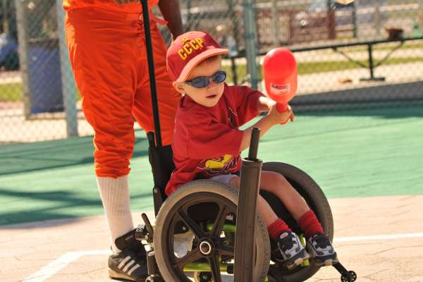 Little boy in wheelchair hits the tee ball with his plastic bat (so cute)