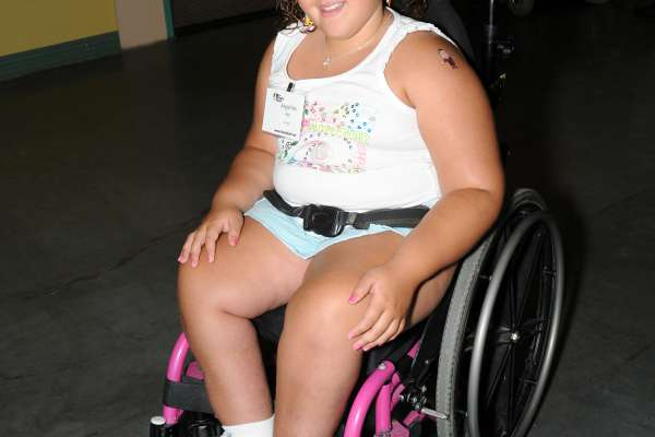 Young girl with curly brown hair smiling for the camera in her wheelchair