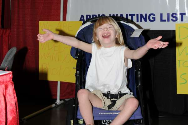 Young girl with develpmental disabilities smiles and opens her arms wide toward the camera